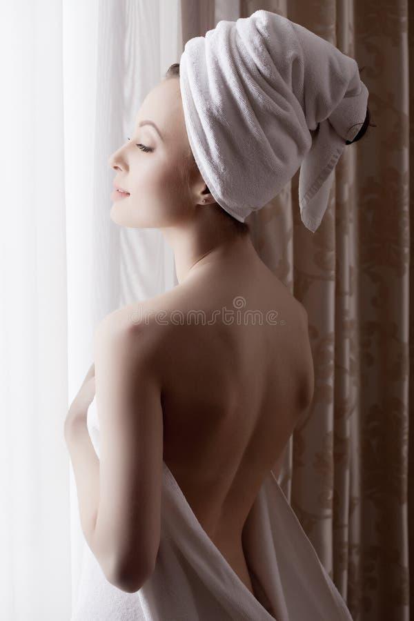 La ragazza seducente si è vestita in asciugamano, posante alla finestra immagini stock