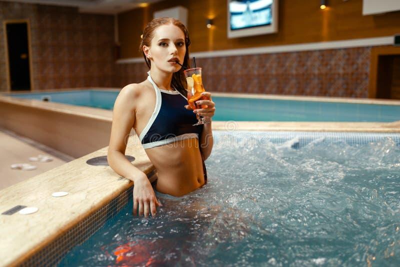 La ragazza sexy beve il cocktail di frutta sul lato dello stagno fotografia stock