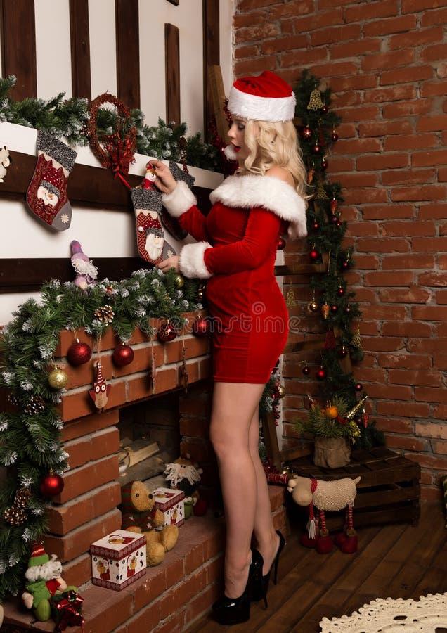 La ragazza sexy di natale nasconde i regali in calzini sul camino donna bionda vestita come Santa immagini stock