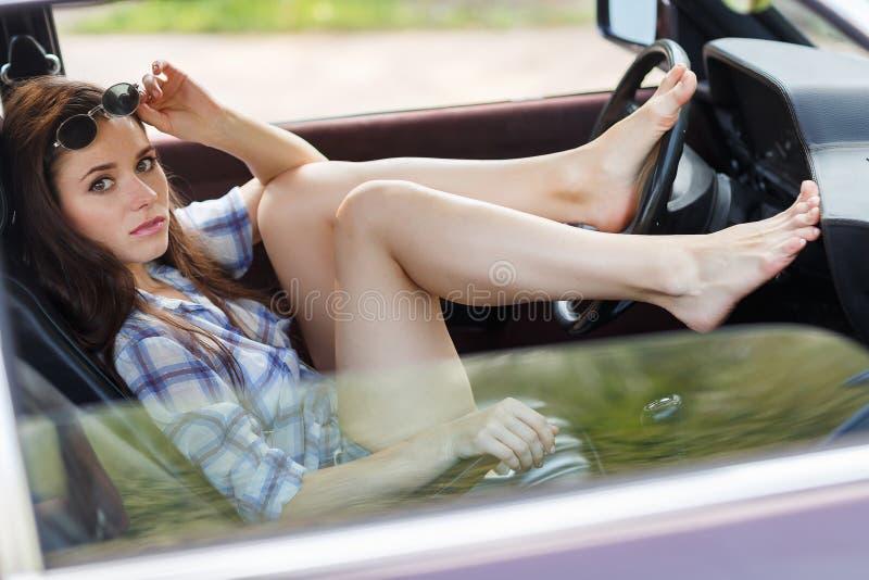 La ragazza sexy ha messo i suoi piedi sopra spinge dentro l'automobile immagine stock libera da diritti