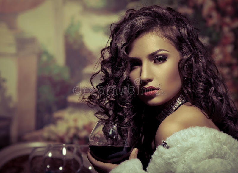La ragazza sexy si siede con vino in pelliccia alla sera immagine stock libera da diritti