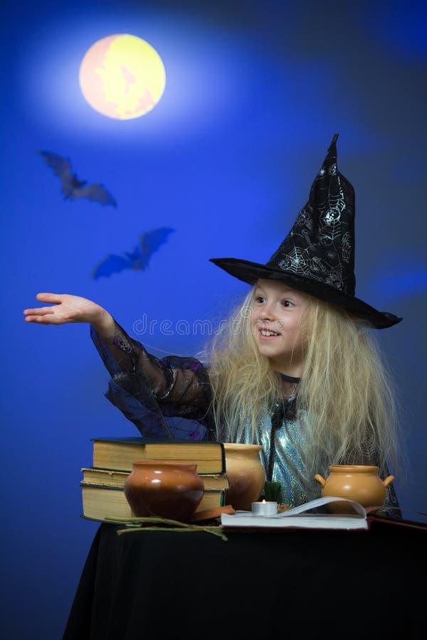 La ragazza si è vestita in su come strega nella notte che fa la magia fotografia stock libera da diritti