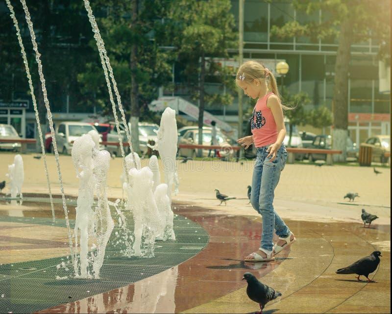 La ragazza si diverte il gioco con acqua in una fontana della città un giorno di estate caldo immagine stock libera da diritti