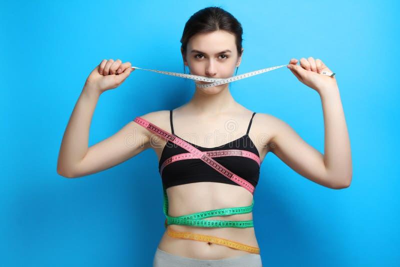 La ragazza si lega con nastro adesivo di misurazione fotografie stock libere da diritti