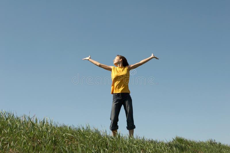 La ragazza si leva in piedi in cima ad una collina immagine stock