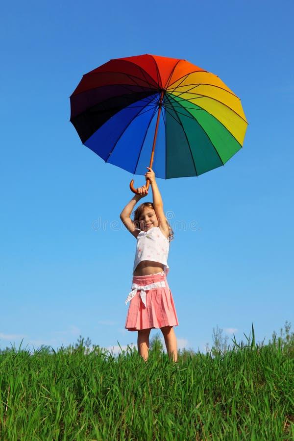 La ragazza si leva in piedi su erba verde con l'ombrello colorato immagini stock