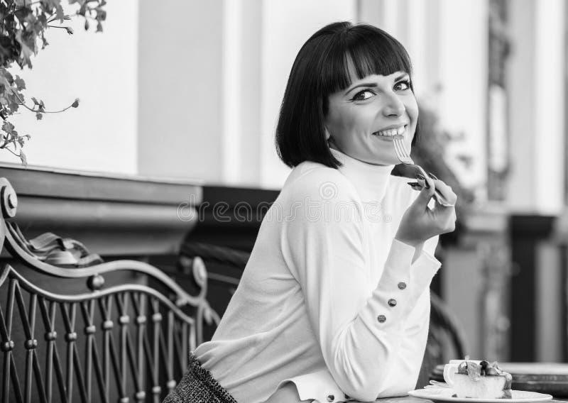 La ragazza si rilassa il caff? con il dessert del dolce Gusto eccellente Castana elegante attraente della donna mangia il terrazz immagine stock