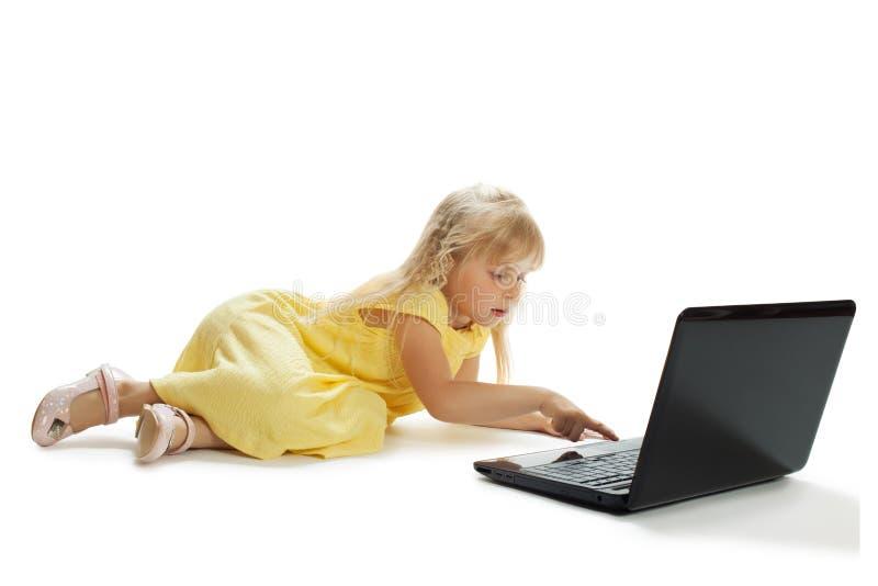 La ragazza si siede ad un computer portatile fotografia stock
