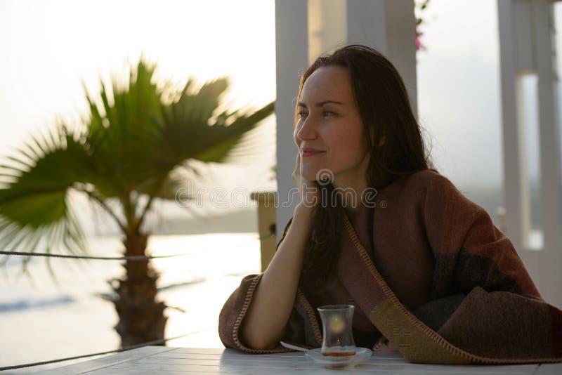 La ragazza si siede ad una tavola su un terrazzo dell'estate alla spiaggia in un plaid ha il tè turco immagine stock