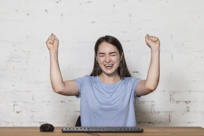 La ragazza si siede alla tavola e si rallegra con le mani sollevate Sta giocando un gioco di computer Sulla tavola c'è una tastie fotografia stock