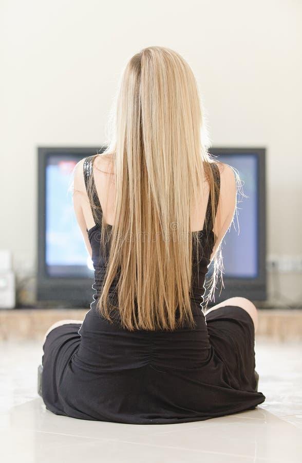 La ragazza si siede contro la grande TV immagine stock libera da diritti