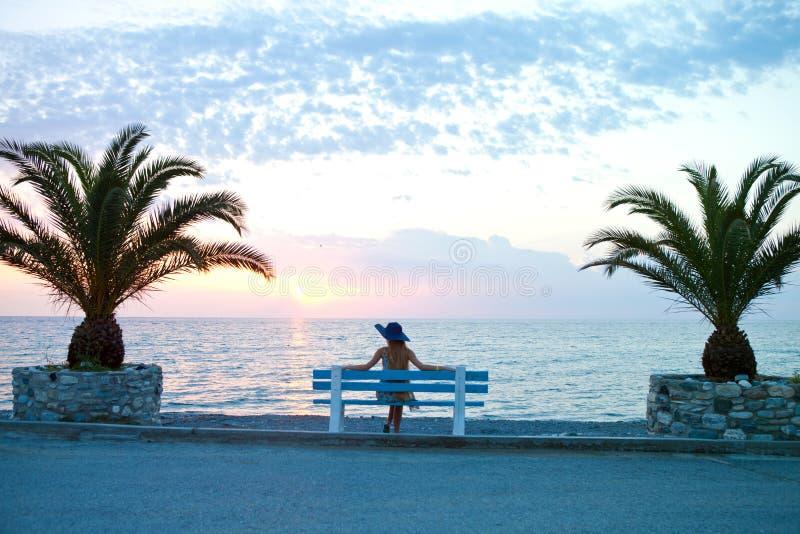 La ragazza si siede l'attesa dal mare fotografia stock