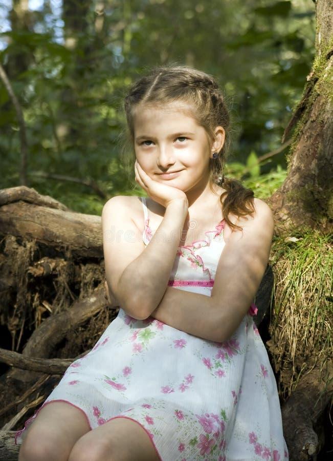 La ragazza si siede in legno immagine stock