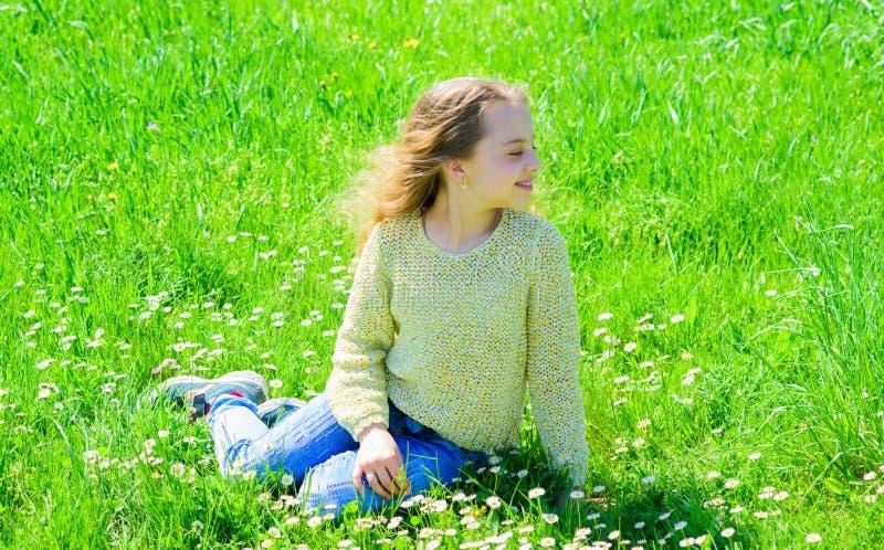 La ragazza si siede su erba a grassplot, fondo verde Il bambino gode del tempo soleggiato della molla mentre si siede al prato pr fotografia stock