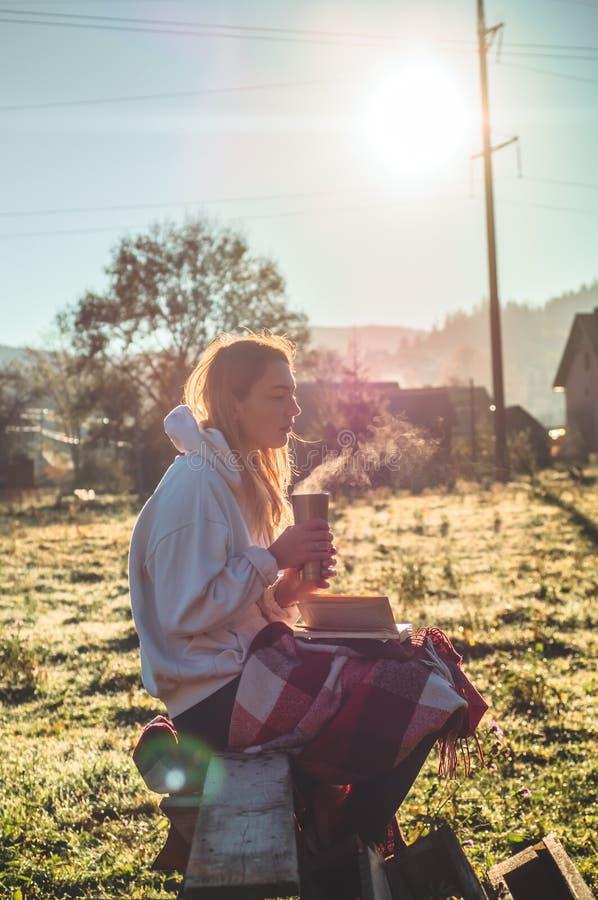 La ragazza si siede su un banco di legno nelle montagne in natura, legge un libro, beve il tè caldo da una termo tazza Concetti c immagine stock libera da diritti