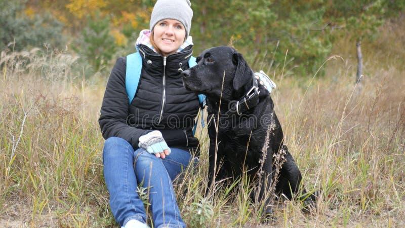 La ragazza si siede su un'erba con un grande cane foto fotografia stock libera da diritti