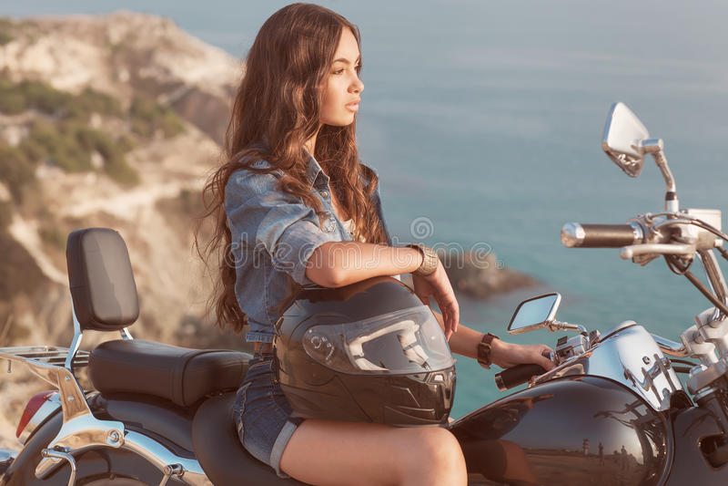 La ragazza si siede su un motociclo. fotografie stock