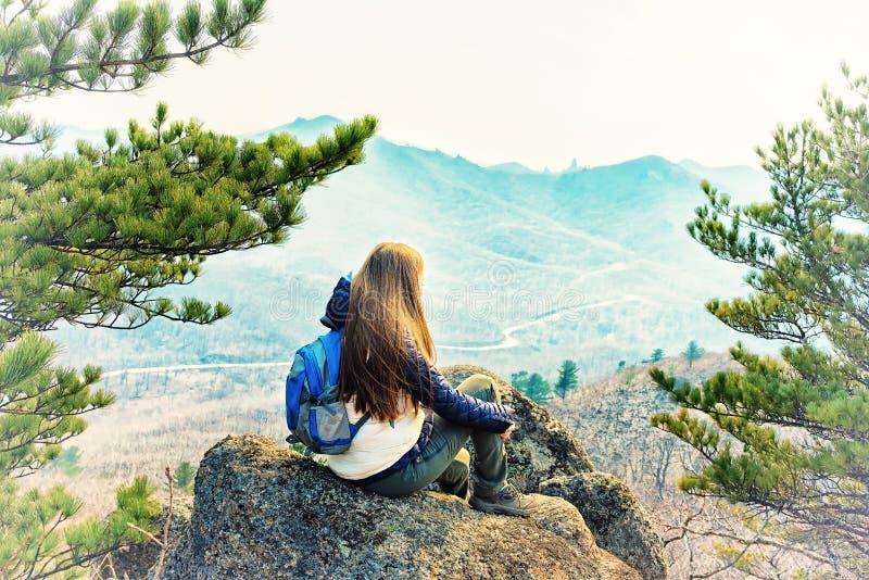 La ragazza si siede su una roccia immagine stock libera da diritti