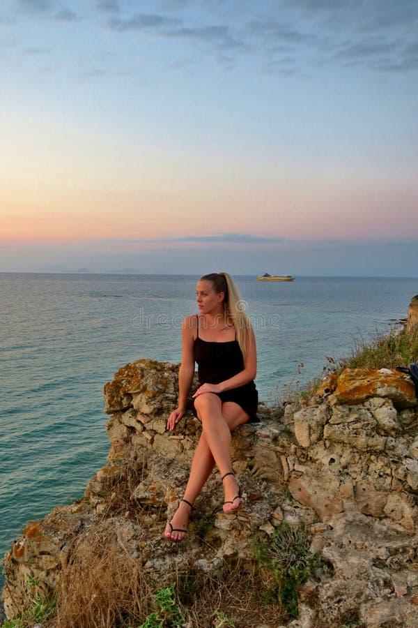 La ragazza si siede su una roccia ed esamina una bella vista del mare e del tramonto fotografia stock libera da diritti