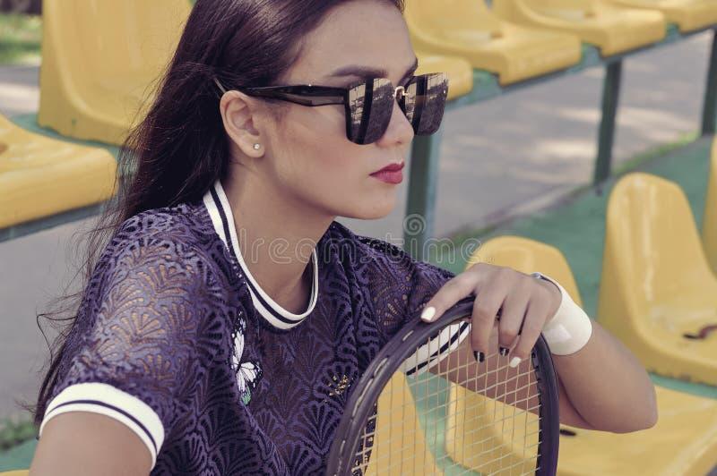 La ragazza si siede sulle tribune spettatori che si appoggiano una racchetta di tennis immagini stock libere da diritti