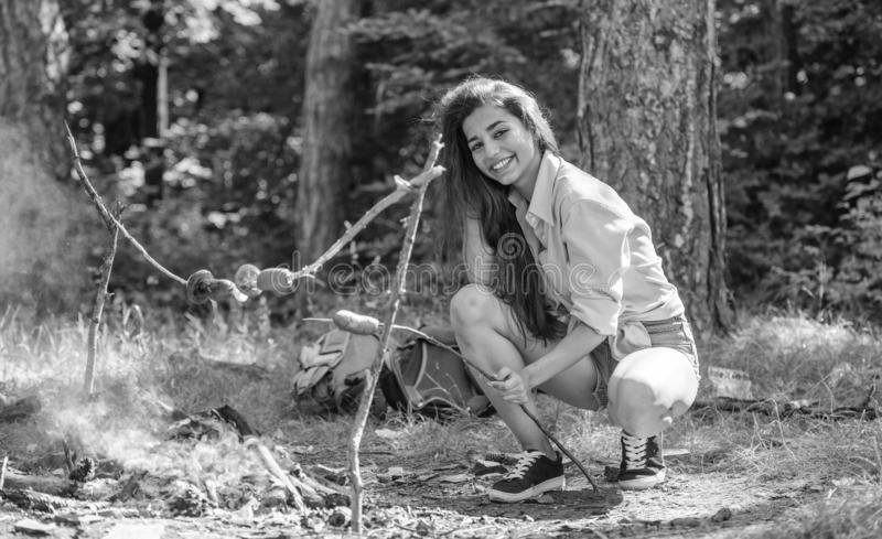 La ragazza si siede vicino alla salsiccia della torrefazione del falò sul bastone Turista della donna che produce alimento sopra  fotografia stock