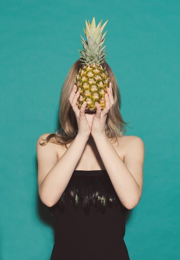 La ragazza si tiene per mano l'ananas, coprente il suo proprio fronte in un vestito nero su un fondo verde nello studio Concetto immagine stock