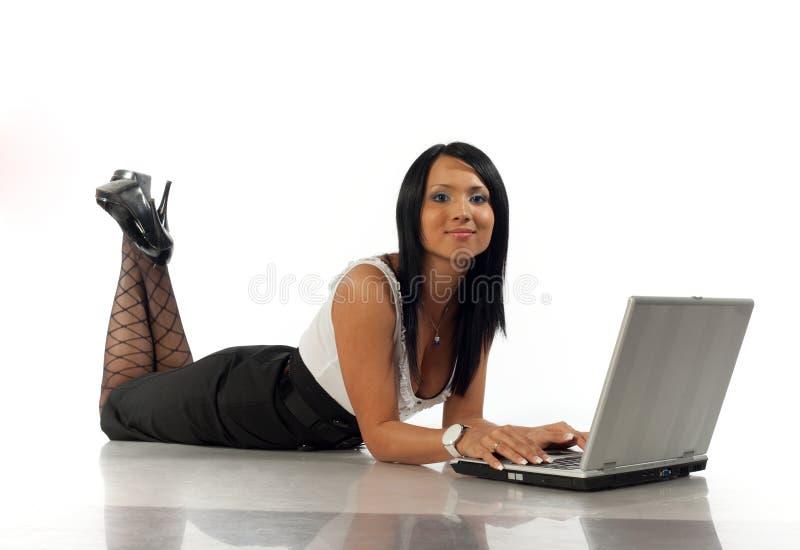 La ragazza si trova con il computer portatile ed il sorriso immagine stock libera da diritti