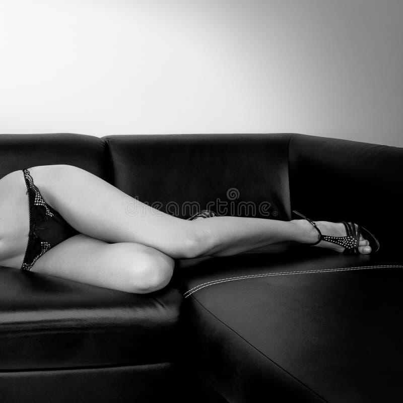 La ragazza si trova sul sofà immagini stock