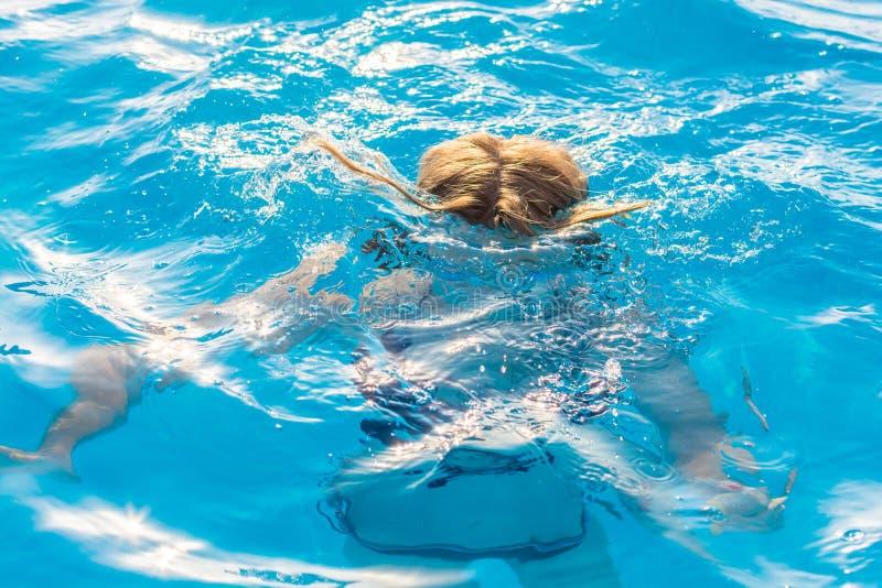 La ragazza si tuffa lo stagno con i vetri per nuotare immagini stock