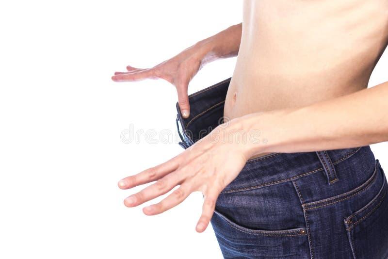 la ragazza snella in grandi jeans mostra la riuscita perdita di peso di suo corpo fotografia stock