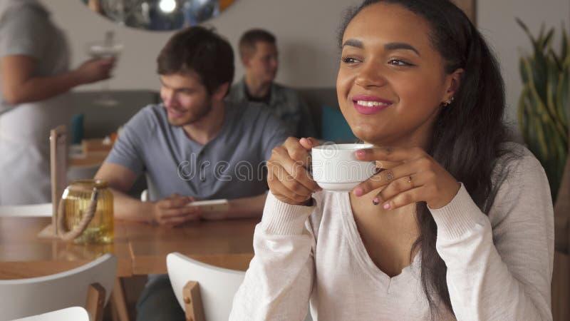 La ragazza sogna sopra la tazza di caffè al caffè fotografie stock libere da diritti