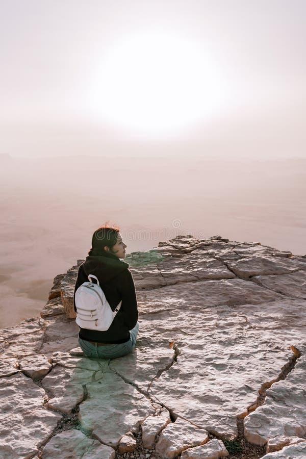 La ragazza sola con lo zaino nel deserto di Negev dell'Israele ammira la vista dell'alba La giovane persona femminile sta sul bor fotografia stock libera da diritti