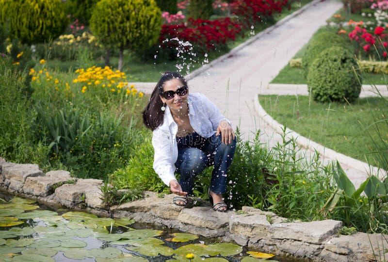 La ragazza sorridente alla fontana fotografia stock