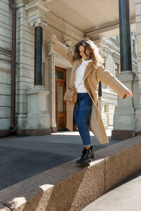 La ragazza sorridente cammina nell'equilibrio sul confine in città soleggiata - concetto di felicità e di libertà per i giovani fotografie stock