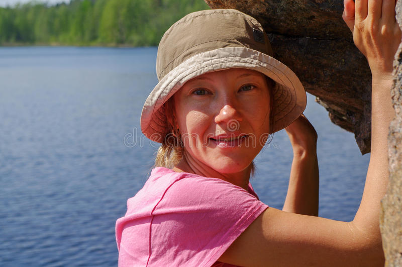 La ragazza sorridente in cappuccio con il amd del lago innaffia il fondo che sta sotto una roccia fotografie stock libere da diritti