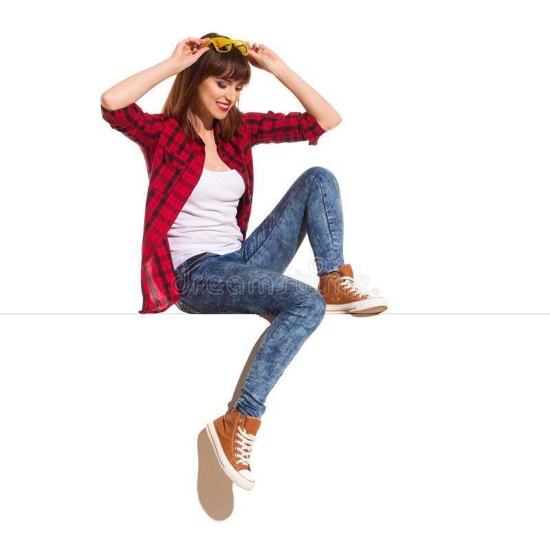 La ragazza sorridente casuale sta sedendosi sulla cima e sta guardando giù fotografie stock libere da diritti