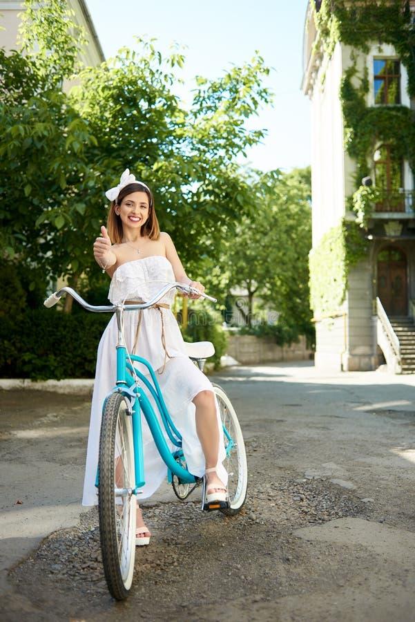 La ragazza sorridente che mostra i pollici su mentre guida un turchese bike immagini stock libere da diritti