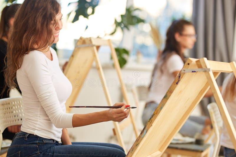 La ragazza sorridente con capelli ricci marroni vestiti in blusa bianca dipinge un'immagine al cavalletto nella scuola di disegno immagini stock libere da diritti