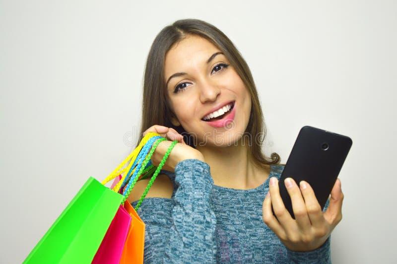 La ragazza sorridente con il cliente insacca sulla suoi spalla e cellulare in sua mano su fondo grigio fotografie stock libere da diritti