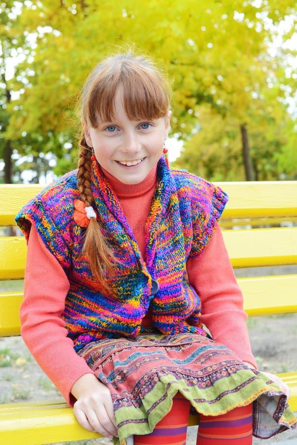 La ragazza sorridente dei pantaloni a vita bassa sta sedendosi nel parco di autunno fotografia stock