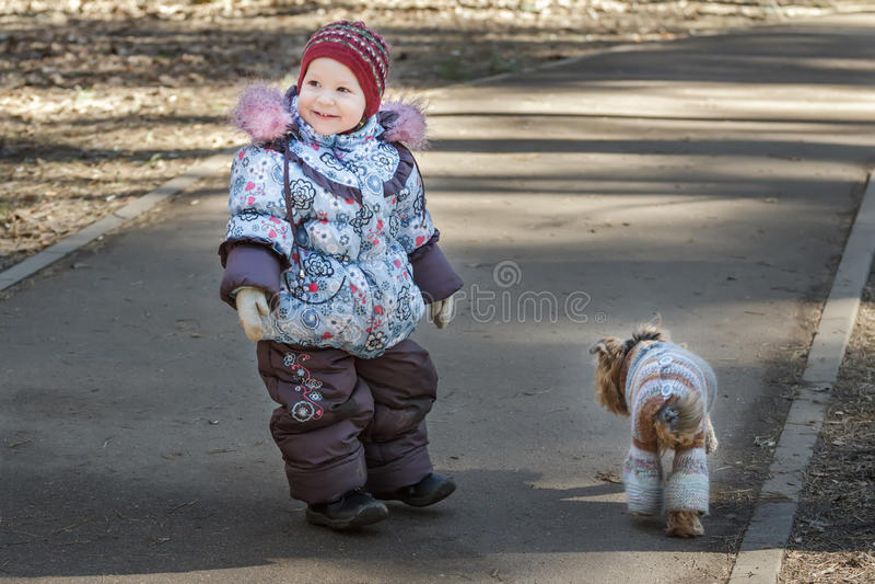 La ragazza sorridente del bambino che cammina con il suo compagno canino si è vestita in cappotto tricottato blu nel parco del fr immagine stock