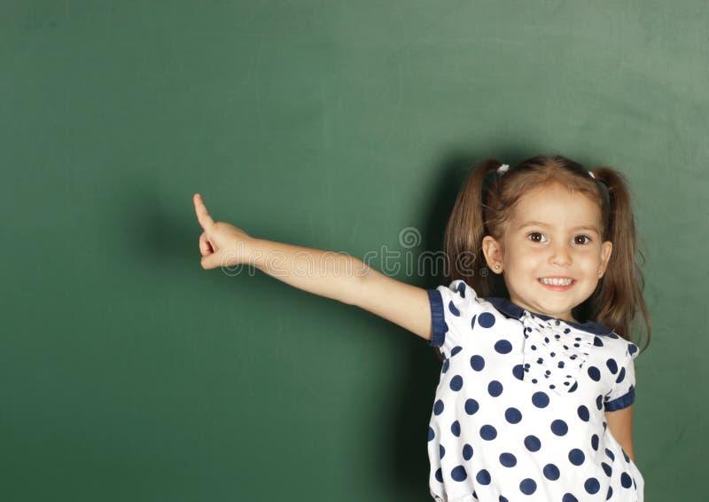 La ragazza sorridente del bambino mostra con una lavagna della scuola dello spazio in bianco del dito, c immagine stock