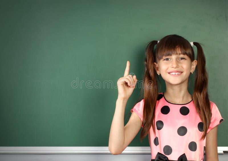 La ragazza sorridente del bambino mostra con una lavagna vuota della scuola del dito, c fotografie stock