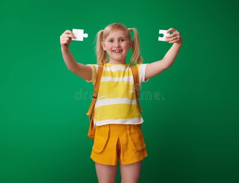 La ragazza sorridente della scuola che mostra il puzzle collega su fondo verde fotografia stock