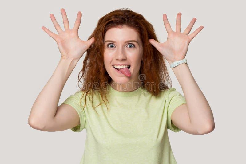 La ragazza sorridente della testarossa gioca i fronti divertenti di mostra insensati fotografia stock