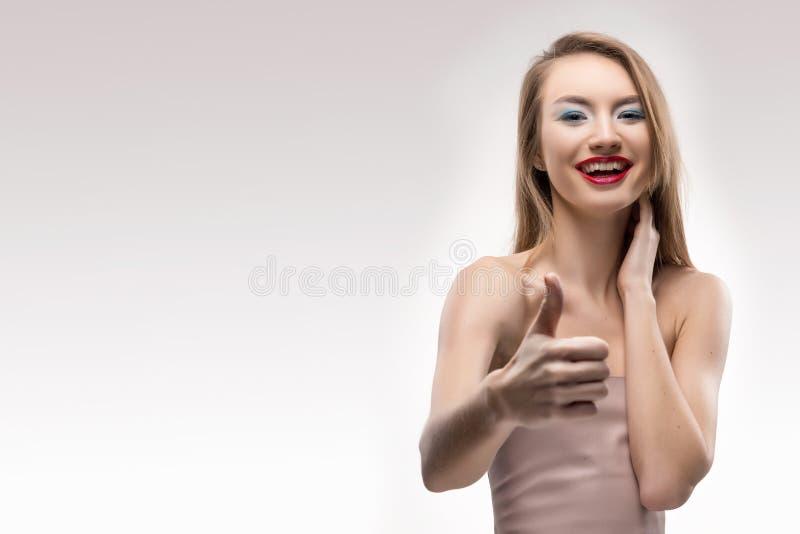 La ragazza sorridente delle belle labbra rosse bionde mostra il pollice del segno fotografia stock