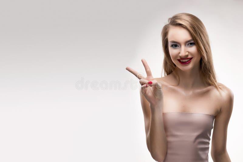 La ragazza sorridente delle belle labbra rosse bionde mostra il vincitore del segno fotografie stock libere da diritti