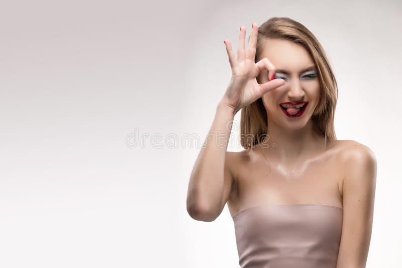 La ragazza sorridente delle belle labbra rosse bionde mostra l'approvazione del segno, quadrata fotografia stock libera da diritti