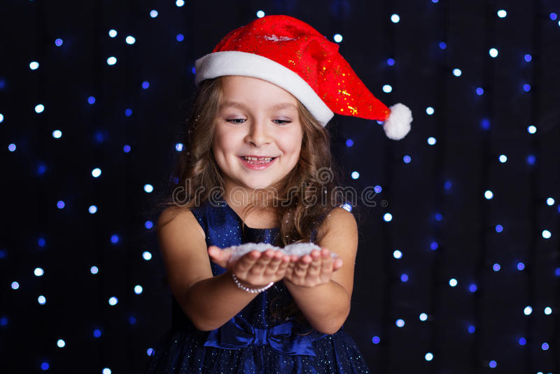 La ragazza sorridente di Santa sta esaminando la neve in mani immagine stock