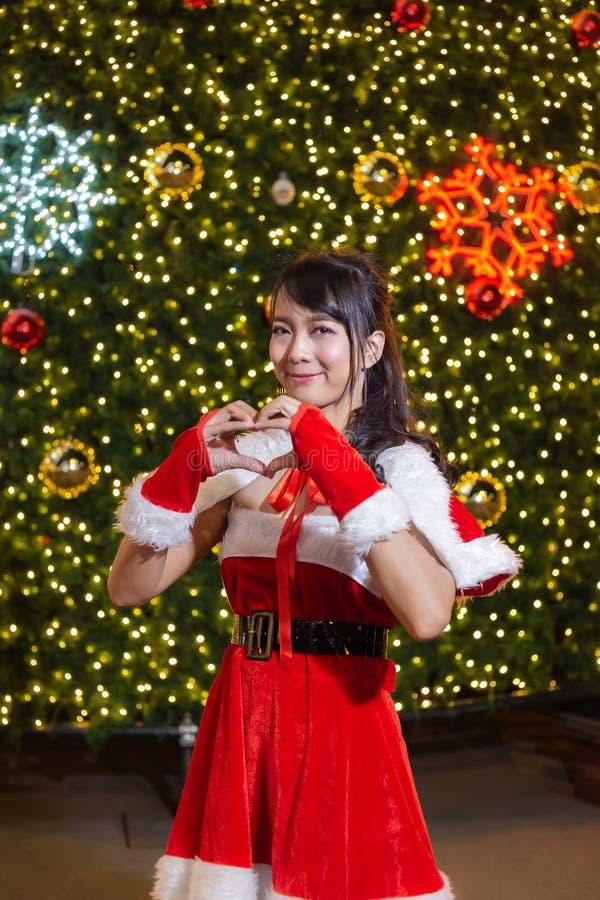La ragazza sorridente felice di Santa è sveglia in vestito rosso e la mano ama il cuore con il fondo dell'albero di Natale immagine stock libera da diritti
